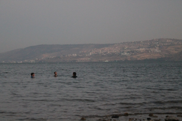 Timothy Chandler, Todd Chandler, and JT Ray relaxing in the Sea of Galilee at sunset. Tiberias is in the background. (Photo by Luke Chandler)